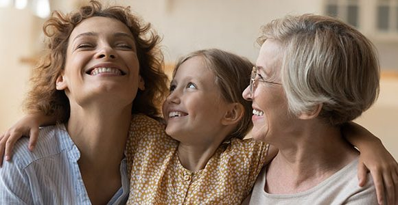 photo of three generations of women on a sofa laughing